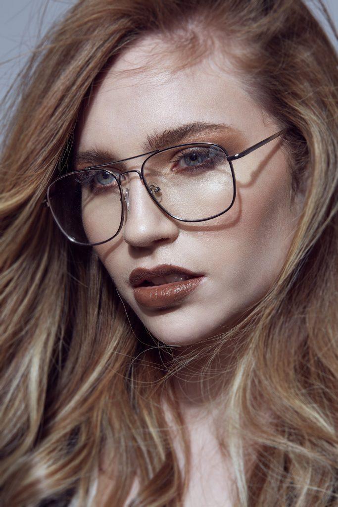 Retrato de moda, modelo con antejos en estudio